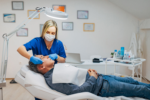 Focused female dermatologist, in her clinic, having a mid adult male patient, with a skin problem, she trying to solve with facial cream and massage