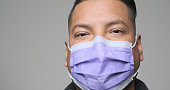 Close up of a Mid adult hispanic man wearing a medical mask coughing  wearing a medical mask on gray background