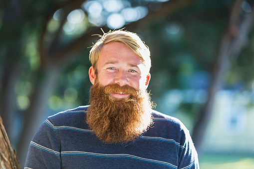 Handsome man with blond hair and a long red beard, standing outdoors on a sunny day.