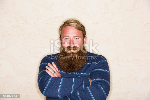 Handsome man with blond hair and a long red beard, standing with arms folded.