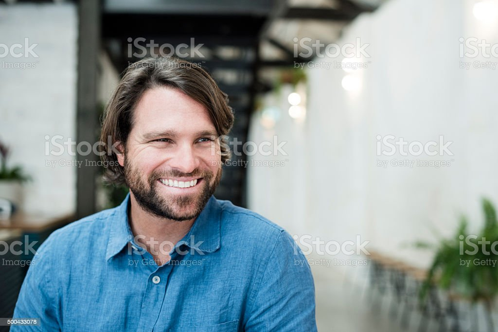 Mid adult man with beard looking away smiling portrait stock photo