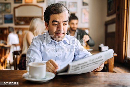 Mid adult man with dwarfism on coffee break in coffee shop reading newspapers