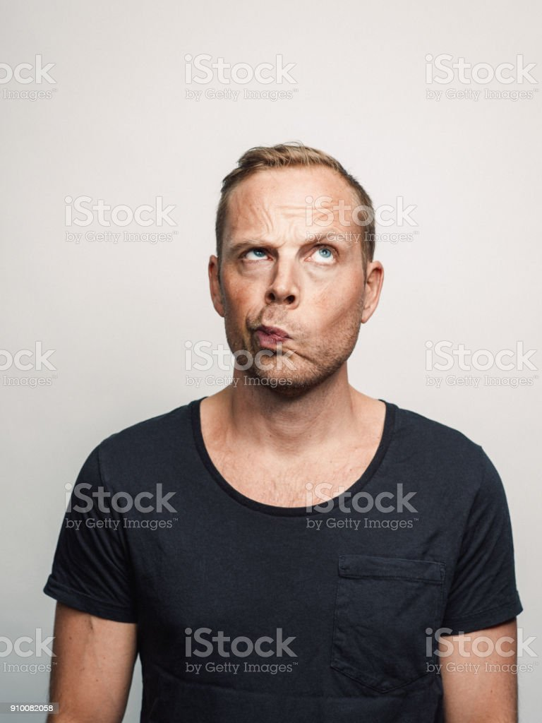 Mid adult man with expression feelings on his face studio shot series sceptic looking up stock photo