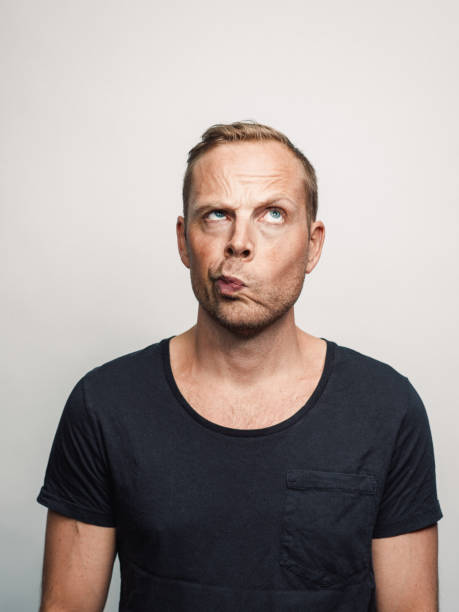 Mid adult man with expression feelings on his face studio shot series sceptic looking up Mid adult man with expression feelings on his face studio shot series. sceptic looking up raised eyebrows stock pictures, royalty-free photos & images