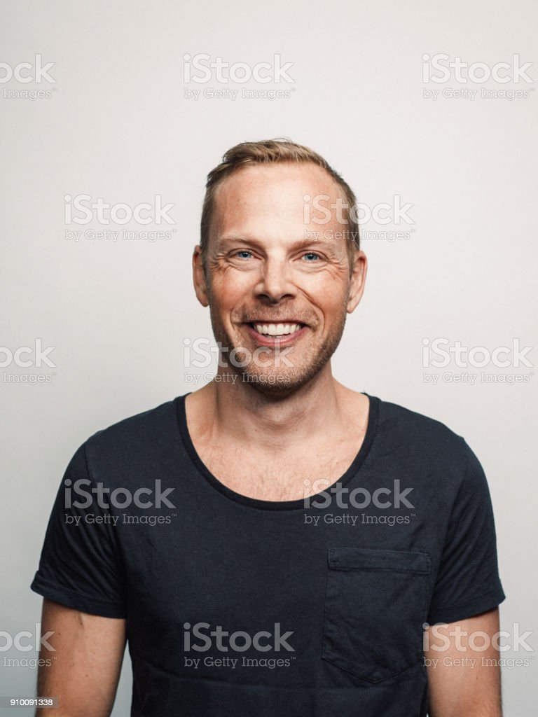 Mid adult man with expression feelings on his face studio shot series happy toothy smile stock photo