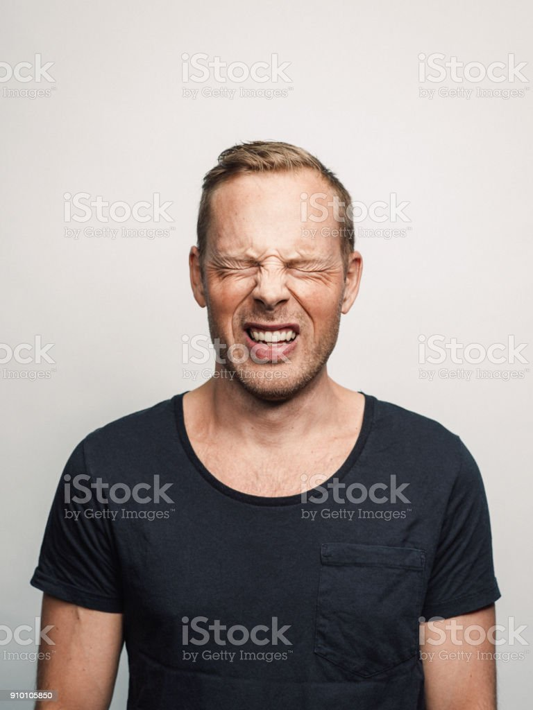 Mid adult man with expression feelings on his face studio shot series in pain eyes closed stock photo