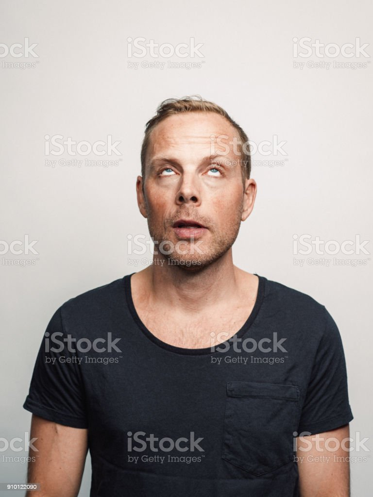 Mid adult man with expression feelings on his face studio shot series rolling his eyes stock photo