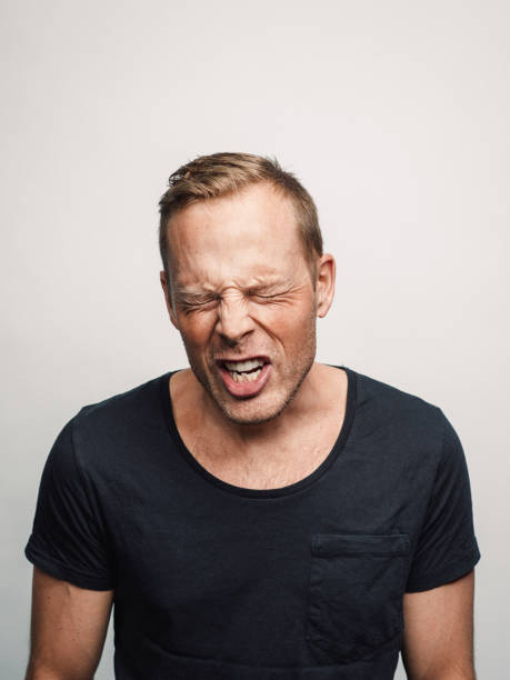 Mid adult man with expression feelings on his face studio shot series sneezing or shouting stock photo