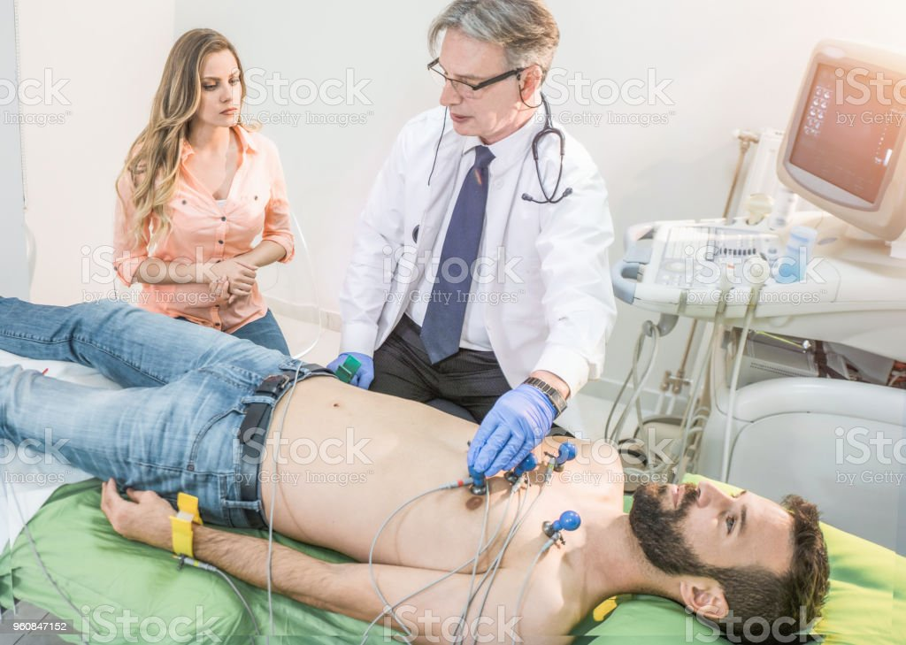 Mid adult man with heart problems on the visit to doctor. stock photo