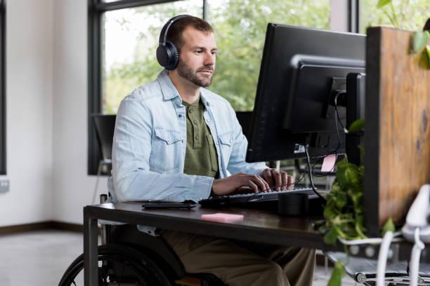 it技術サポートデスクで働くミッドアダルト男性 - disabilitycollection ストックフォトと画像