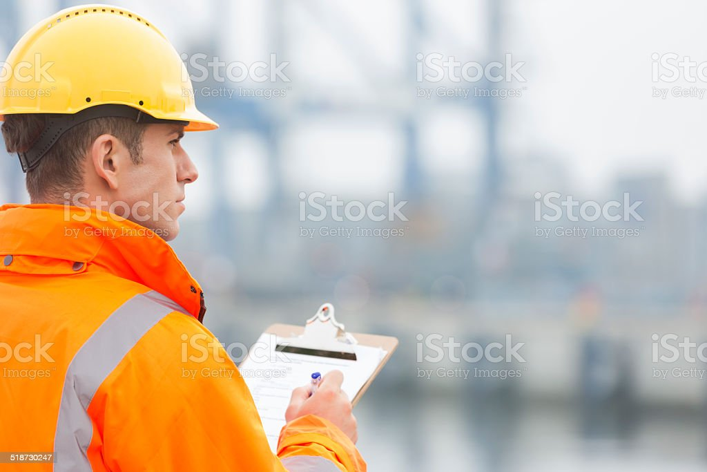 Mid adult man writing on clipboard in shipping yard stock photo