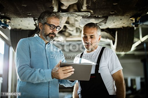 1137474295 istock photo Mid adult manager and auto mechanic using touchpad in a workshop. 1183904229