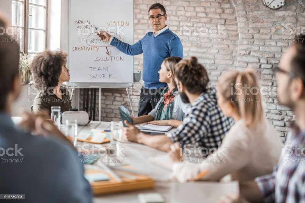 Mid adult manager giving a presentation to his colleagues in the office. stock photo