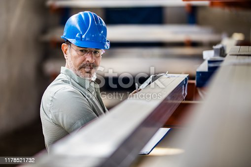 Mid adult quality control inspector working on labels of manufactured products in a factory.