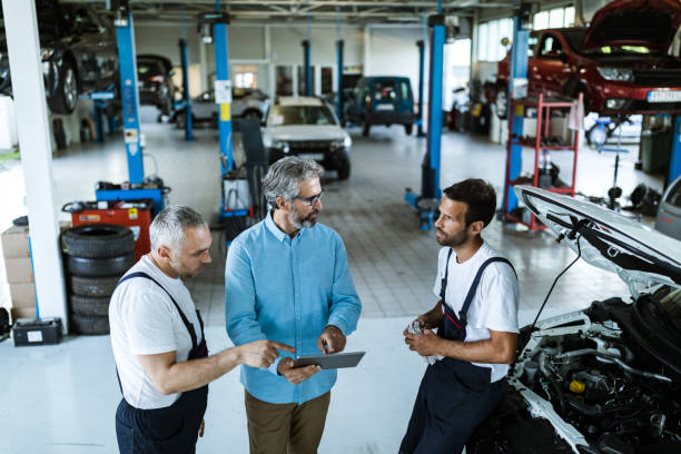Mid adult manager using touchpad and talking to car mechanics in a workshop. Mid adult manager using digital tablet while talking to mechanics in auto repair shop. auto repair shop stock pictures, royalty-free photos & images