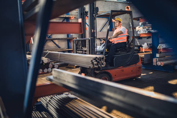 Mid adult manual worker driving a forklift in a metal factory. stock photo