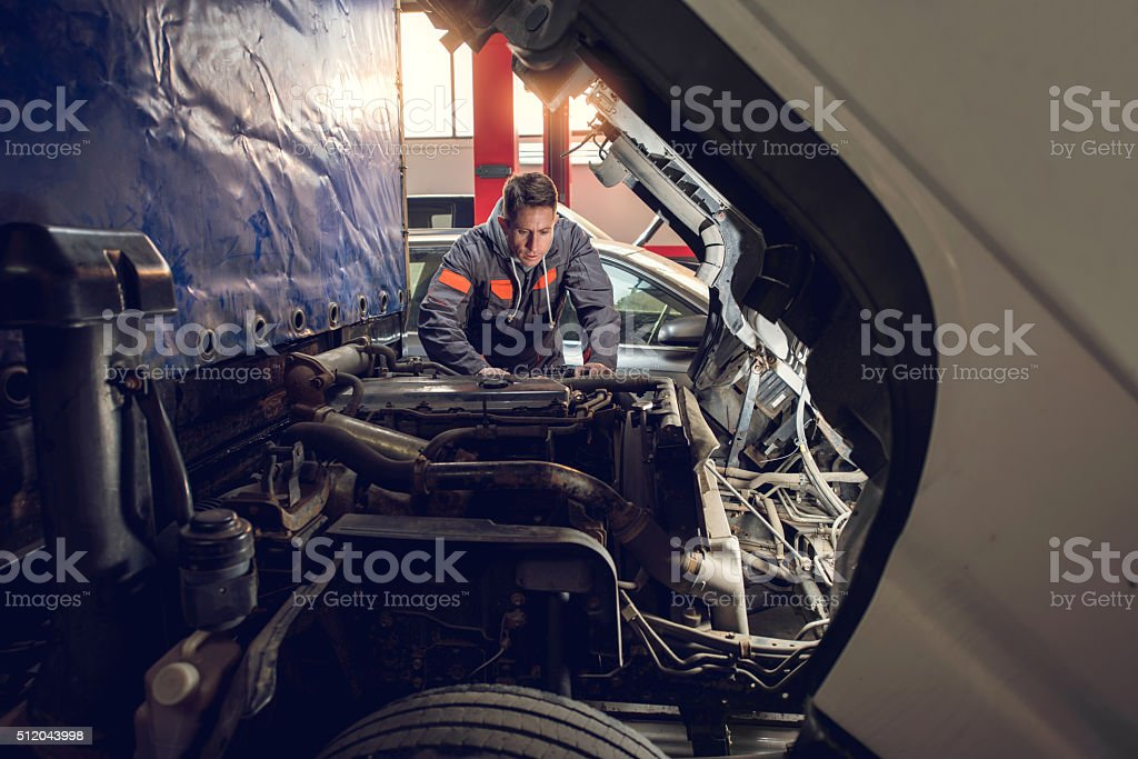 Mid adult mechanic repairing a truck in auto repair shop. stock photo