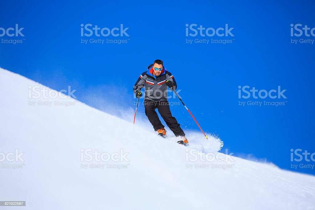 Mid adult  men snow skier skiing on sunny ski resorts stock photo