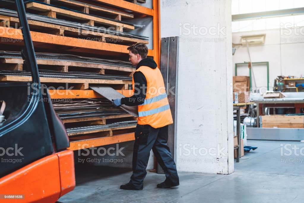 Mid adult metal worker working in a factory stock photo