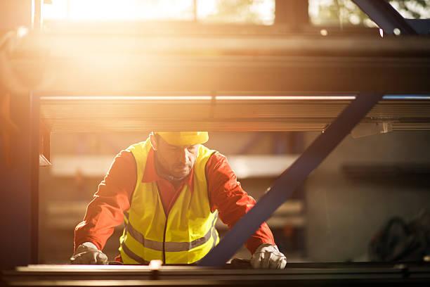 Mid adult metal worker working in industrial building. stock photo