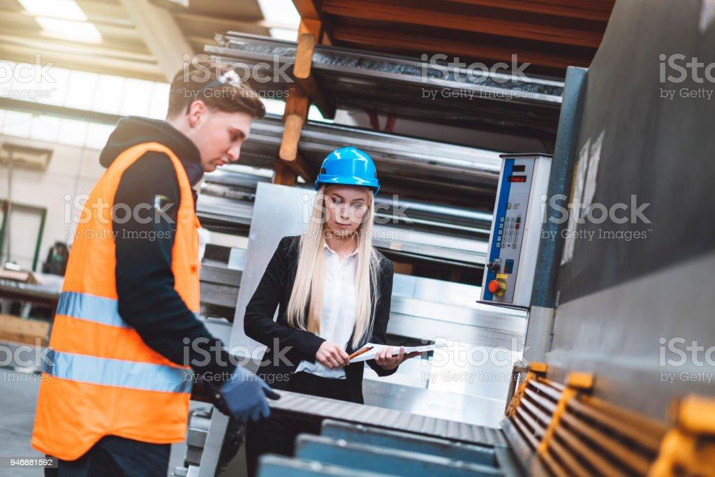 Mid adult metal worker working in industrial building stock photo