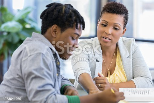 The mid adult mom invests time to teach her son.  She is pointing something out to him on his work.