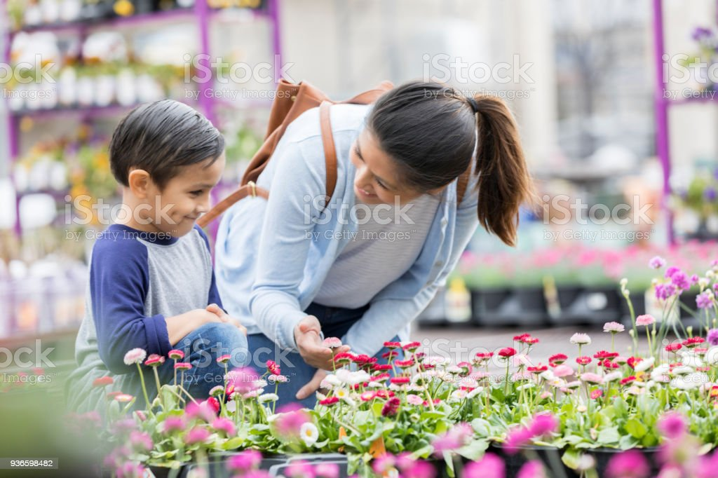 Mid adult mom talks with her preschool age son while they shop for...