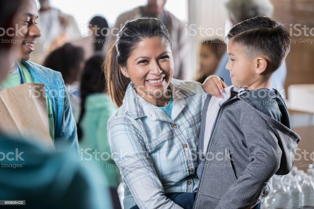 Mid adult mother adjusts son's jacket at food bank stock photo