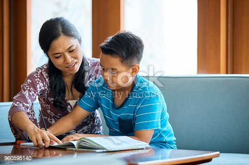 istock Mid adult mother assisting son in studying at home 960595140