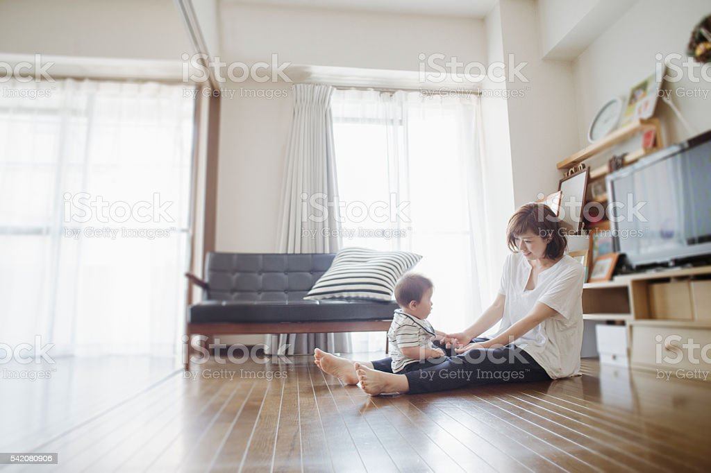 Mid adult mother loving her baby boy at home. stock photo