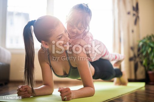istock Mid adult mother practicing yoga with toddler daughter on top of her, beautiful mother and daughter training home workout 1142601353