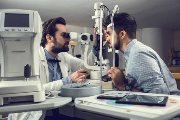 Mid adult ophthalmologist measuring an eyesight of a young man with diagnostic medical tool. stock photo
