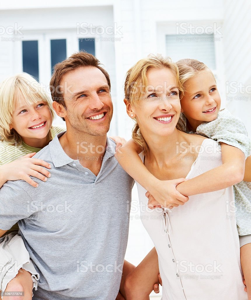 Mid adult parents carrying their kids on back royalty-free stock photo