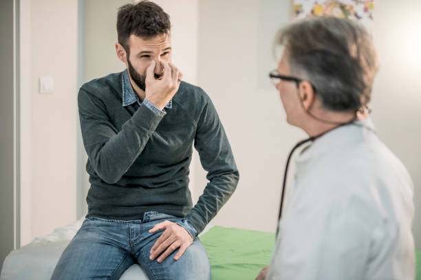 mid adult patient describing his breathing problem to a doctor. - naso foto e immagini stock