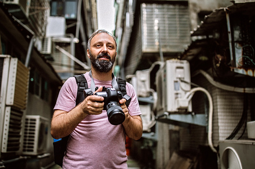 Mid adult photographer in city alley