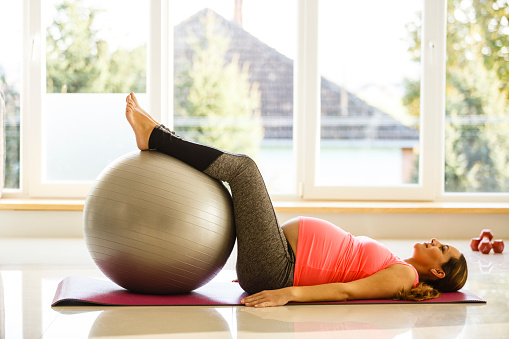 istock Mid adult pregnant woman is exercising with a fitness ball 670407790