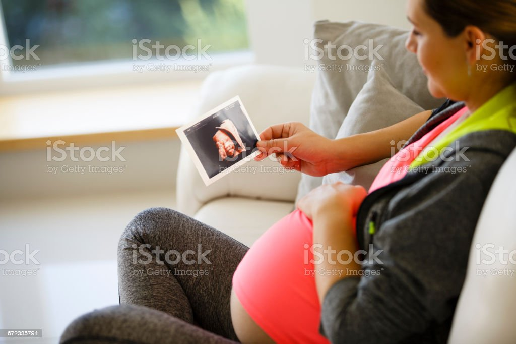 Mid adult pregnant woman is looking at ultrasound picture of her baby stock photo