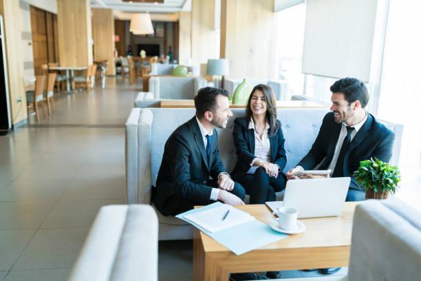 Mid Adult Professionals teilen einen leichten Moment in der Lobby – Foto