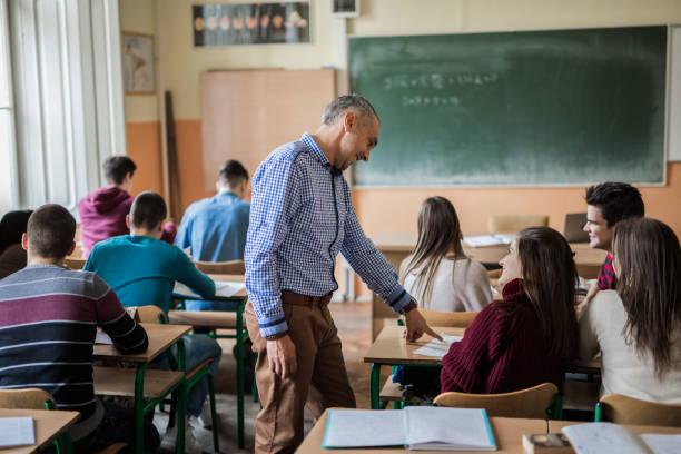 mid adult professor helping his students during a class at high school. - professore di scuola superiore foto e immagini stock
