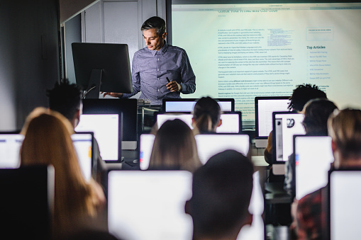 Mid adult professor teaching a lecture from desktop PC at computer lab.