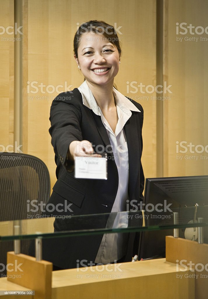 Mid adult receptionist handing out Visitor Name Badge royalty-free stock photo