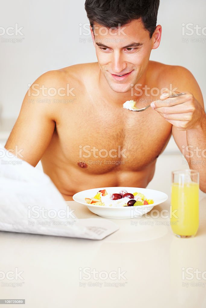 Mid adult shirtless guy eating salad and reading newspaper royalty-free stock photo