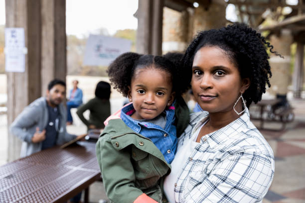 Mid adult single mother holds young daughter at free clinic While the volunteer doctor watches in the background, the mid adult single mother holds her young daughter and looks at the camera. serious stock pictures, royalty-free photos & images