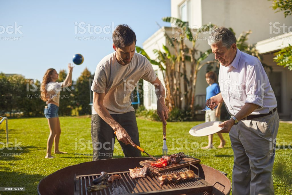 Mid adult son is serving barbecued meat to his senior father. Family lifestyle in Buenos Aires 30-39 Years Stock Photo