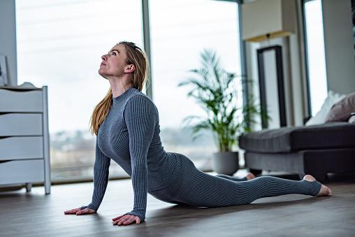 Beautiful woman practicing yoga, lying in Cobra pose, Bhujangasana.