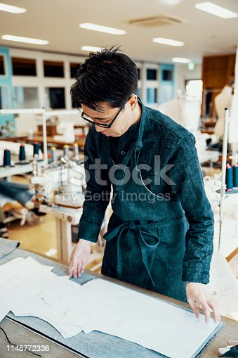 Mid adult tailor cutting denim around a pattern in preparation to make a pair of jeans by hand in Japan