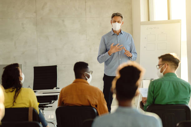 Mid adult teacher with protective face masks talking to a group of university students in lecture hall. stock photo