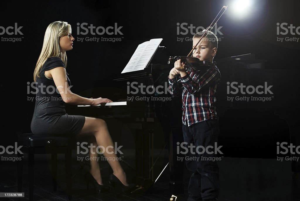Mid adult woman and boy playing musical instruments on stage. stock photo