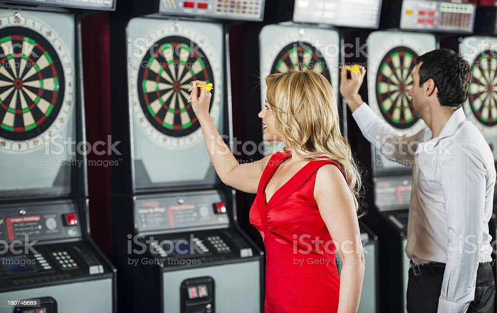 Mid adult woman and man playing darts. royalty-free stock photo