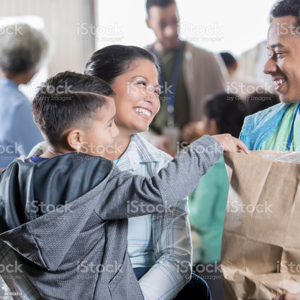 Mid adult woman and young son receive groceries at food bank stock photo